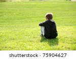 Sad abandoned orphan sitting in nature and contemplating, autism syndrome - stock photo
