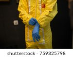 Scientist or inventor wears decontamination suit of yellow color, puts on blue rubber gloves to protect skin, looks like chemist