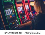Small photo of Slot Machine Casino Playing. Caucasian Woman in Her 30s Playing Modern One Handed Bandit Slot.