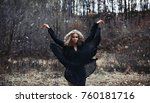 Small photo of A girl in a black dress heaved up hands upwards on a background the dark forest