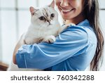 Stock photo cropped image of beautiful female doctor veterinarian is holding cute white cat on hands at vet 760342288
