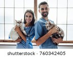 Stock photo handsome doctor veterinarian and his attractive assistant at vet clinic are holding cute cats on 760342405