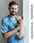 Stock photo handsome male doctor veterinarian at clinic is holding little dog yorkshire terrier on hands and 760342435