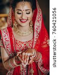 Small photo of Stunning Indian bride dressed in Hindu red traditional wedding clothes lehenga embroidered with gold and a veil smiles tender holding something in her hands