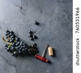 Small photo of Bunch of fresh ripe dark blue Isabella grapes with old corkscrew and cork over black texture background. Top view with space. Food background. Square image
