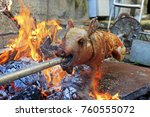 suckling pig on a rotating spit ... | Shutterstock . vector #760555072