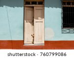 Small photo of Dog peeping head out of door in colorful building, colonial city of Trinidad cuba.