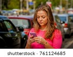 A portrait of a beautiful Caucasian girl sending a text message to her boyfriend who is late for their date.