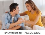 Small photo of Understanding woman. Pretty cheerful young woman supporting her husband while sitting and listening to his story