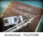 Vial And Vintage Syringe With Medicine On An Old Book Of Capital Punishment, Conceptual