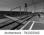 Small photo of black and white photo of railway wagons Laden with goods is on the station on the background of railway tracks. summer, bright sun and blue sky. rail waypoint arrow and semaphores