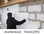 Small photo of Builder installing rigid styrofoam insulation board for energy saving. Rigid extruded polystyrene insulation.