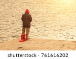 man in a red hood is fishing... | Shutterstock . vector #761616202