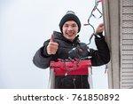 man hanging christmas lights...   Shutterstock . vector #761850892