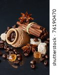 Coffee beans, brown cane sugar, anise and cinnamon on a shiny black. - stock photo