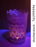 Small photo of White floral patterned pot with candle inside illuminated after dark