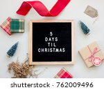 Small photo of 5 Days Til Christmas. Christmas countdown on a black letter board with wooden frame surrounded by holiday objects.