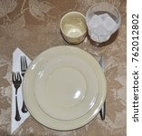 Small photo of Full table setting. Dinner Plate, Salad Plate Forks, knife, coffee cup, water goblet. Ready for a meal.