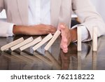 Small photo of Businesswoman Hand Stopping Wooden Blocks From Falling On Desk At Office