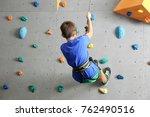 young boy climbing wall in gym | Shutterstock . vector #762490516