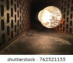 Small photo of Light bulb set inside an old industrial lamp shade