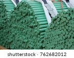 three stacks of green reinforcement bars bundled together re bar - stock photo