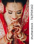 Small photo of Stunning Indian bride dressed in Hindu red traditional wedding clothes lehenga embroidered with gold and a veil