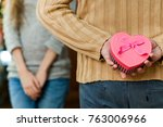 Small photo of couple in love celebrate valentine's day. Man making surprise on holiday to his pretty wife. Wife close her eyes and waiting for present. Concept of happy valentine's day