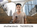 asian man play phone looking in ... | Shutterstock . vector #763305136