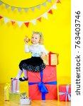 little girl in a dress sits on... | Shutterstock . vector #763403746