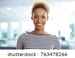 Small photo of Close-up of a young afro-american casual businesswoman standing in the office.