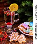 Small photo of Christmas glass latte mug and Christmas multicolored cookies on plate with fir branches. Mag decoration lemon slice on wooden table in restaurant. Cookie is slide.