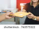 Small photo of male hand send mail envelope to the female of post office before sending