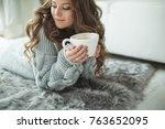woman in a sweater drinking tea  | Shutterstock . vector #763652095