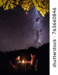 Small photo of ABEL TASMAN COAST, NEW ZEALAND april 25 2017: two unidentified travelers are having dinner under a tree with the milky way on the background