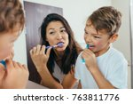 Mother And Son Brushing Teeth...