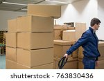 man carries boxes by pallet... | Shutterstock . vector #763830436