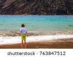 kid looking at the ocean in a... | Shutterstock . vector #763847512