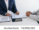 Small photo of Businessman being analysis and making the decision a car insurance policy, Agent man is using calculator to presentation detail and waiting for his reply to finish.