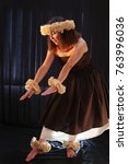 Small photo of beautiful Hawaiian dancer with flowers and diverse outfit and playing ukulele, on black background