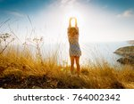 Small photo of A girl heaved up hands, in a colorful dress. On a background the sea waves summer. Vacation.