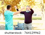 young caregiver walking with... | Shutterstock . vector #764129962