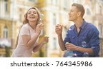 optimistic young couple blowing ... | Shutterstock . vector #764345986