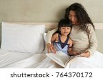 asian woman reading in bed with ... | Shutterstock . vector #764370172