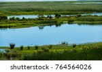 Small photo of Blue marsh waters and green grasses abound in the Marshes