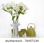 Vase with alstroemeria and green chinese teapot on white background - stock photo
