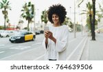 Small photo of Freelancer female waiting for a taxi she called by a mobile phone app. Smiling student girl chatting online while relaxing outdoors with a music downloaded and played on a smartphone.