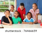 Group of smiling school children at classroom desk - stock photo