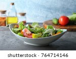 plate with fresh tasty salad on ... | Shutterstock . vector #764714146