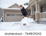 teenage boy shoveling driveway | Shutterstock . vector #764819242